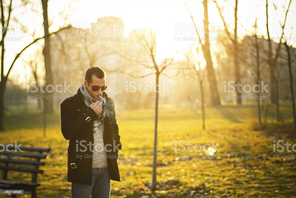Young man smoking cigarette in the golden park royalty-free stock photo