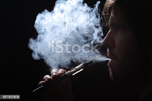 689660424 istock photo Young man smoking electronic cigarette on black background 537302828