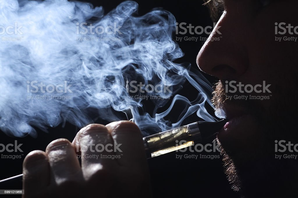 Young man smoking electronic cigarette on black background stock photo