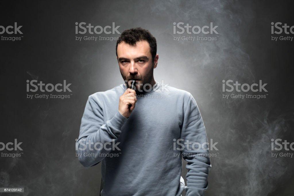 年輕男子吸煙電子煙 免版稅 stock photo