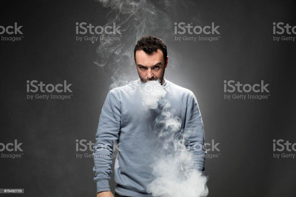 Jeune homme fumer cigarette électronique photo libre de droits