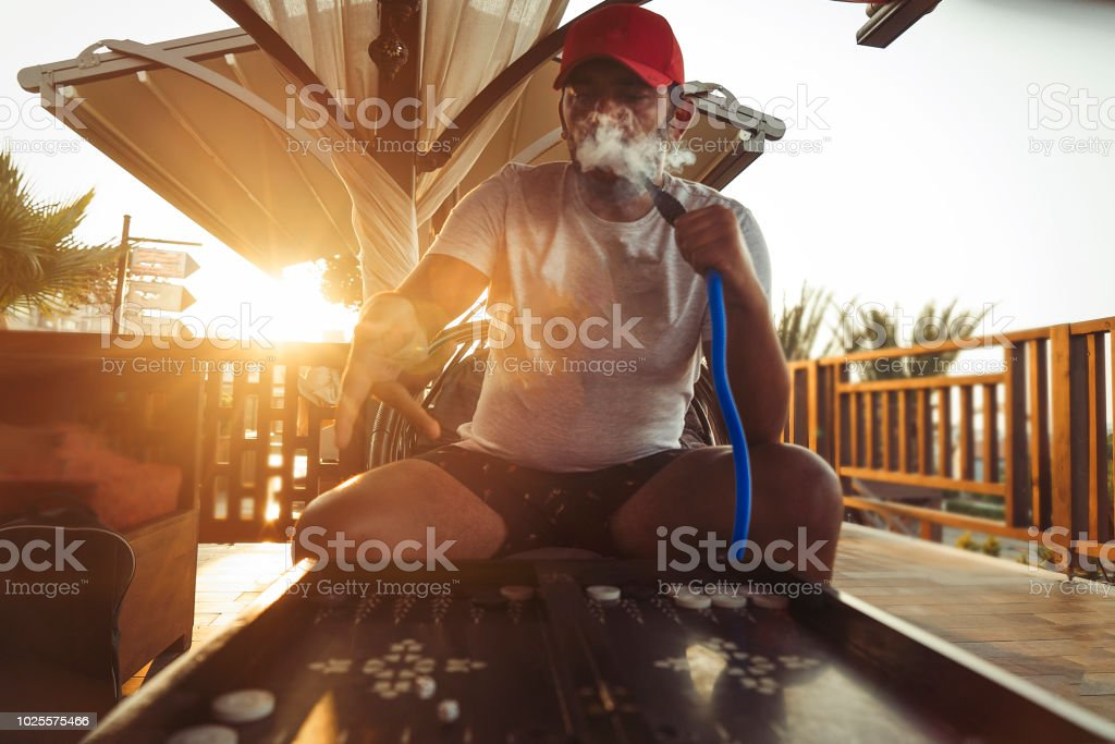 Young man smoking hookah and playing backgammon stock photo