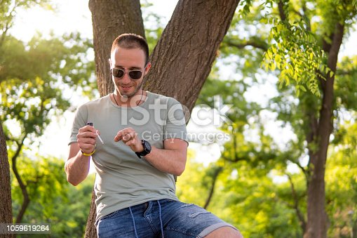 istock Young man smoking in public park 1059619264