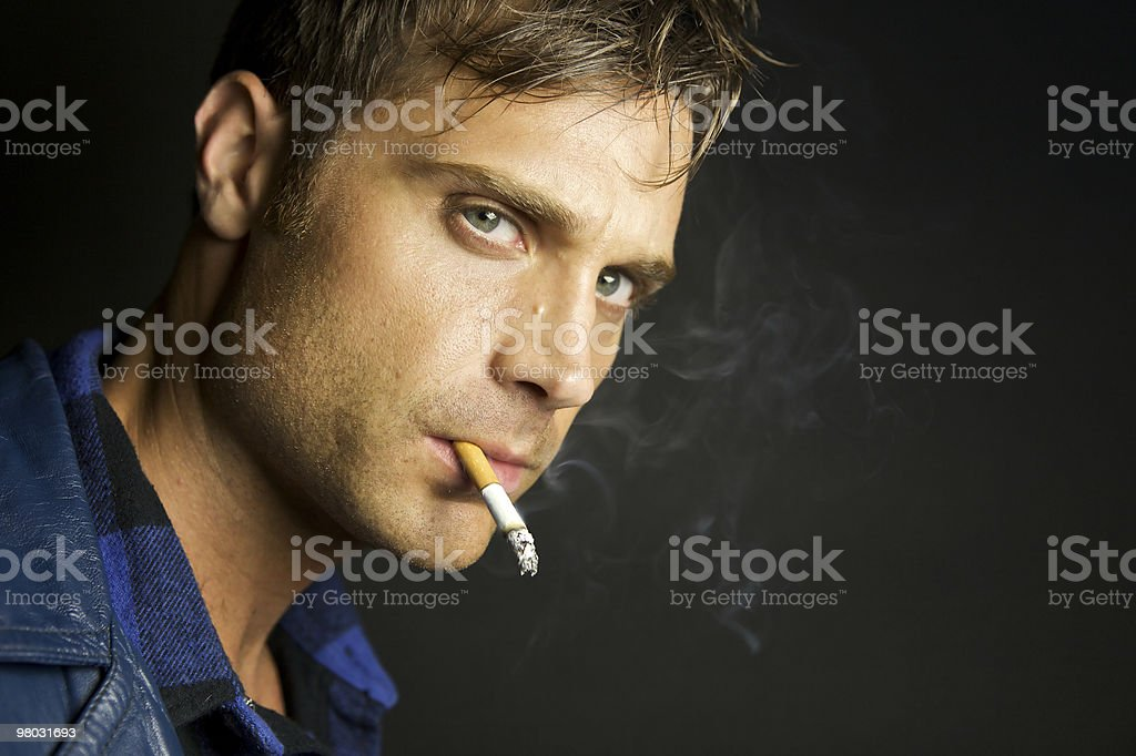 Young Man Smoking With A Serious Look royalty-free stock photo