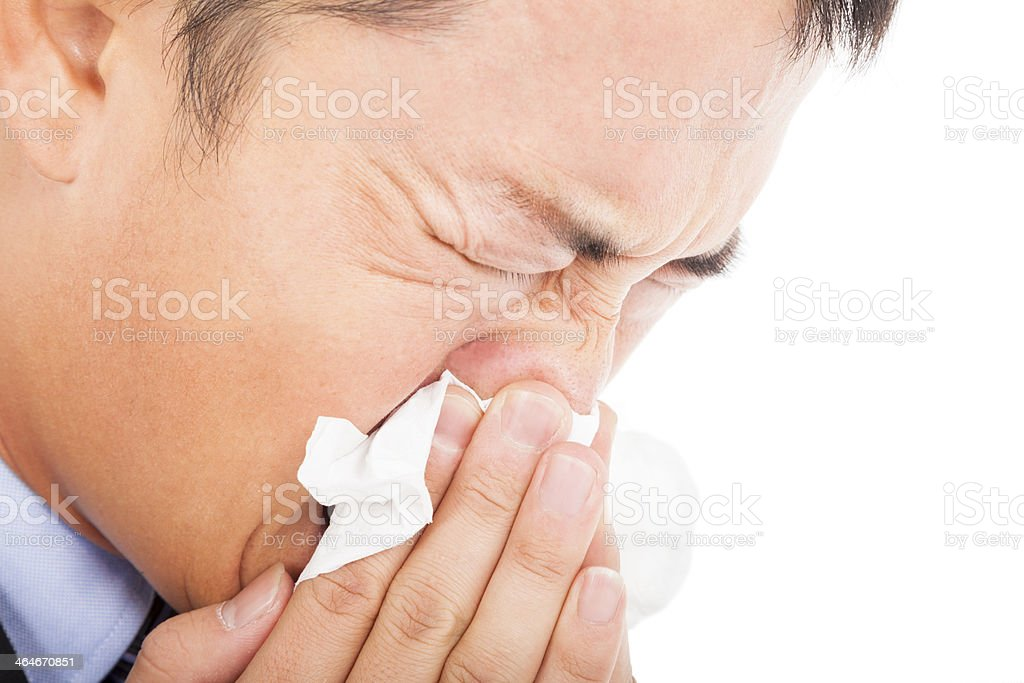A young man sneezing into a tissue stock photo
