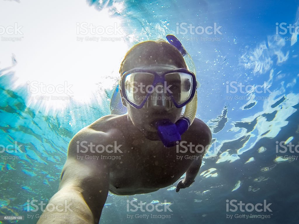 Young man snorkeling in the ocean - Canary Islands, Spain. stock photo