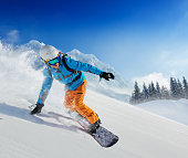 Young man snowboarder running down the slope in Alpine mountains. Winter sport and recreation, leasure outdoor activities.