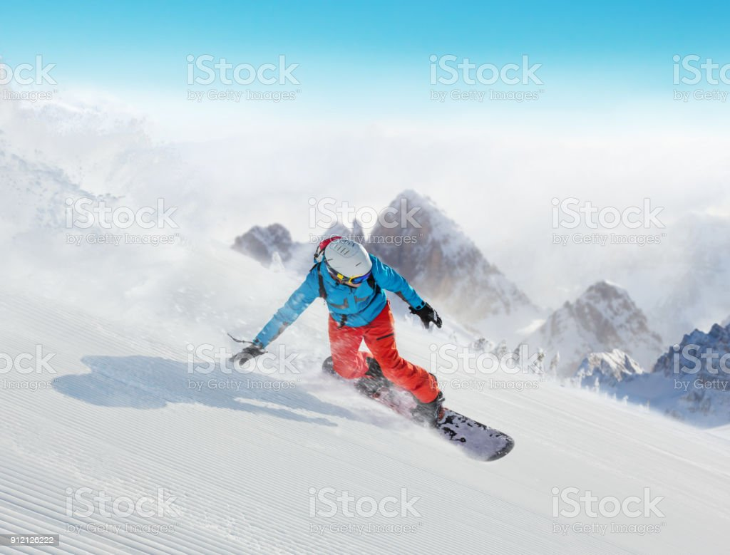 Young man snowboarder running downhill in Alps stock photo