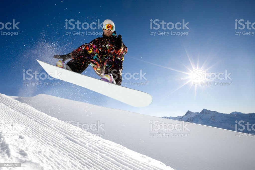 Young Man Snowboarding in Half Pipe on Sunny Day