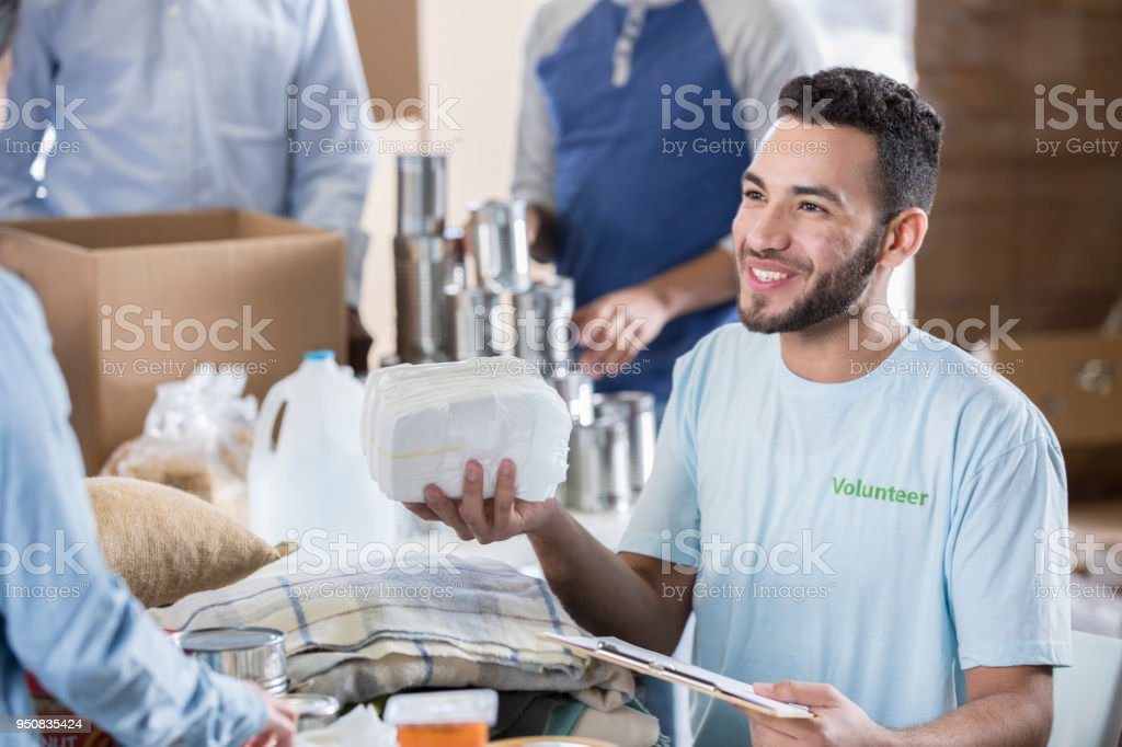 Jeune homme trie les couches et linge de maison à la Banque alimentaire  locale photo libre 8235f80a429