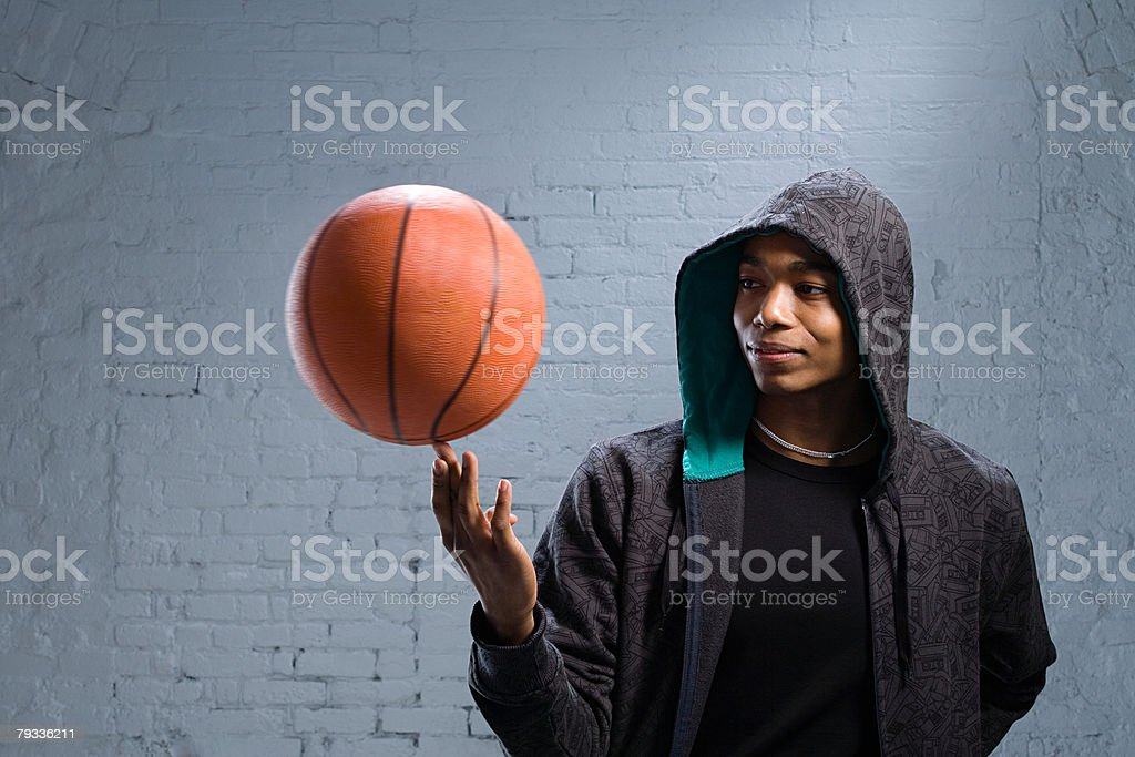 Young man spinning basketball stock photo