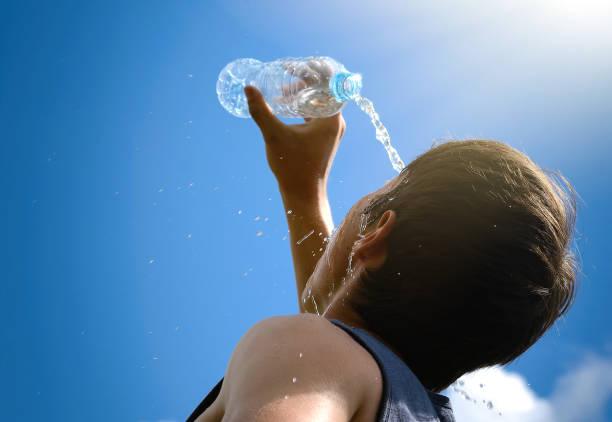 Jeune homme aux éclaboussures et verser de l'eau douce provenant d'une bouteille sur son visage. - Photo