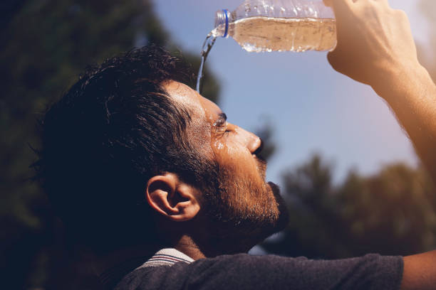 Young man splashing and pouring fresh water from a bottle on his head to refresh against a blue sky background in a summer heat stock photo