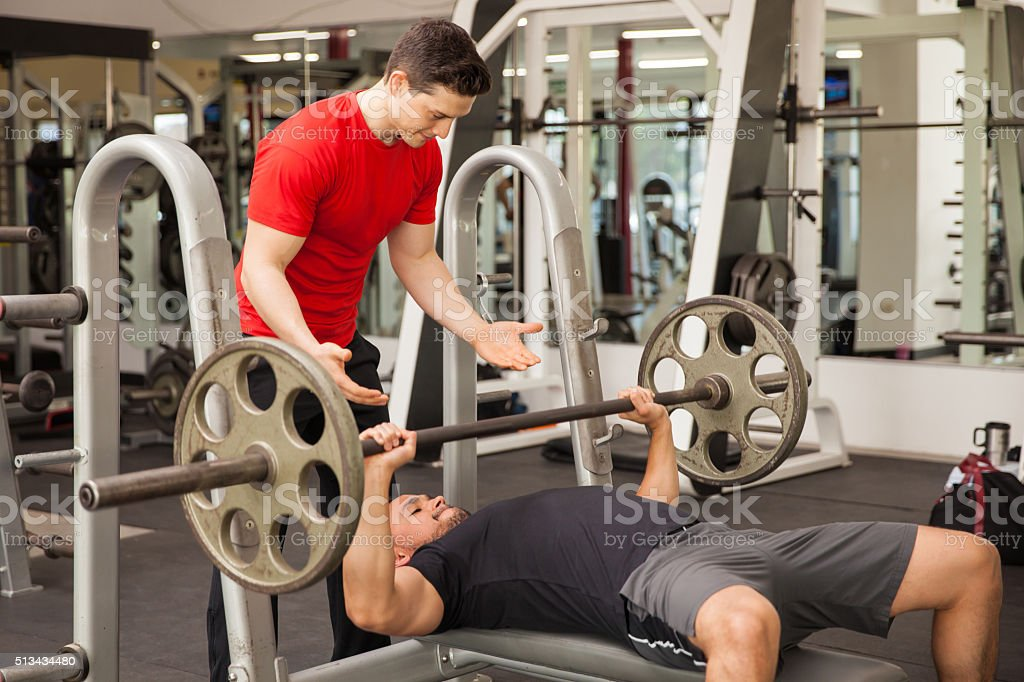 Young man spotting each other in a gym stock photo