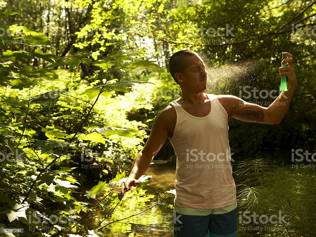 Young man spraying bug spray stock photo