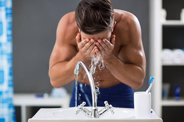 Young man spraying water on his face after shaving stock photo