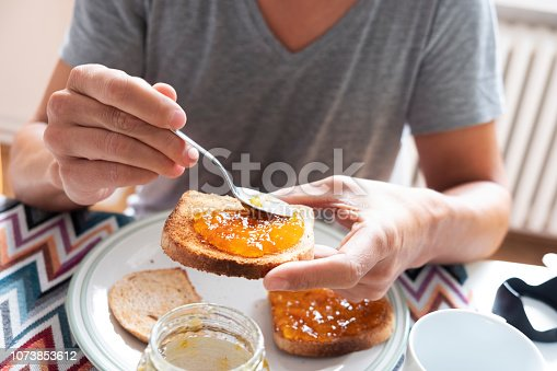closeup of a young caucasian man, wearing a casual gray T-shirt, sitting at a set table, spreading some orange or peach jam on a toast