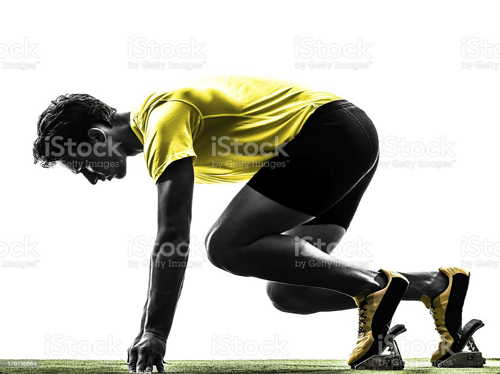 young man sprinter runner in starting blocks silhouette stock photo
