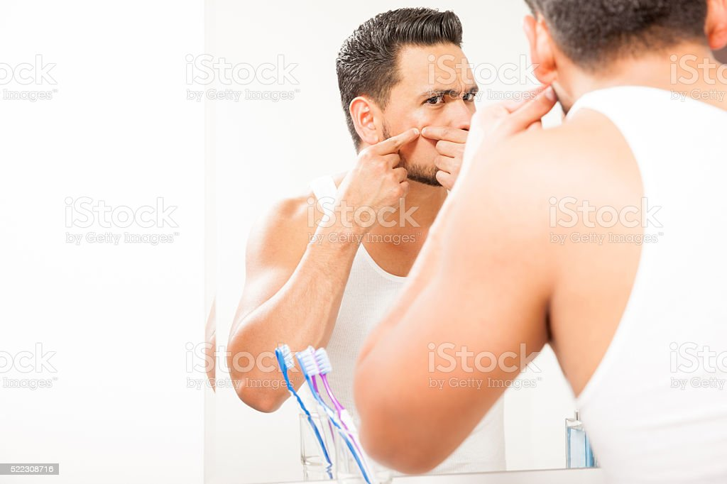 Young man squeezing a pimple stock photo