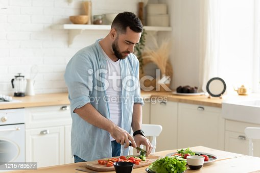 istock Young man stand in kitchen cooking salad for lunch 1215789577