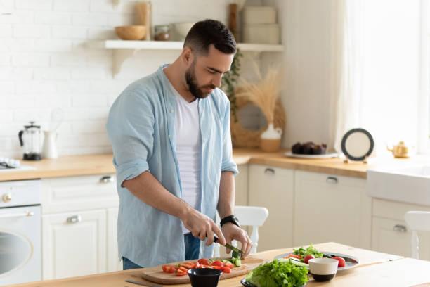 Joven de pie en la cocina cocina cocinar ensalada para el almuerzo - foto de stock