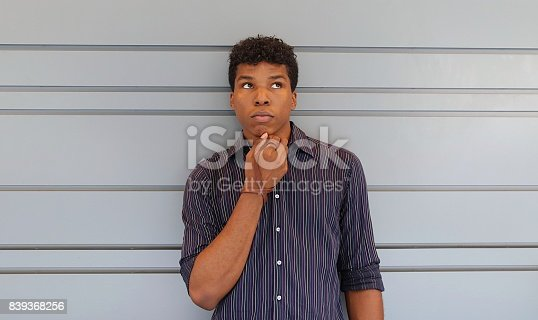 istock Young man standing against a gray wall 839368256