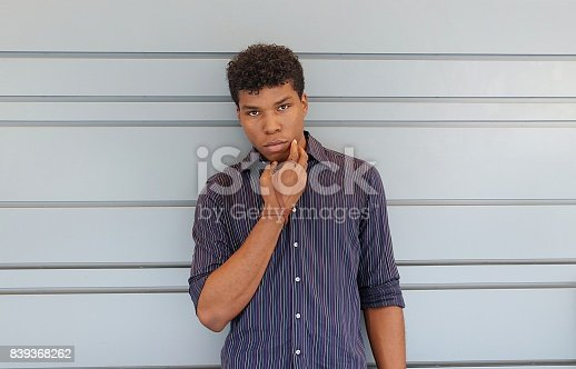 istock Young man standing against a gray wall 839368262
