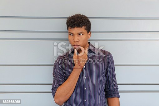 istock Young man standing against a gray wall 839368268