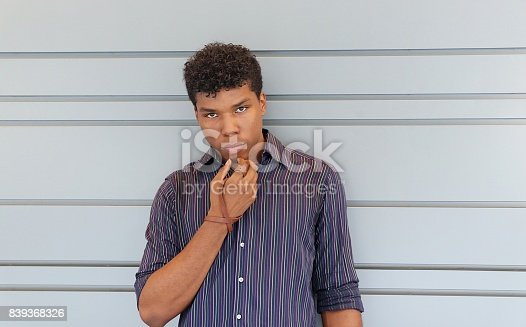 istock Young man standing against a gray wall 839368326