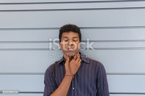 istock Young man standing against a gray wall 839368530