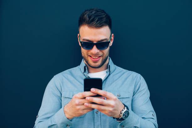 Junger Mann steht gegen blaue Wand auf Bildschirm des Smartphones und lächelt – Foto