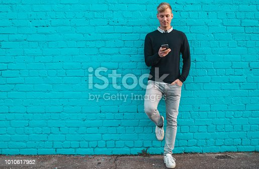 Young man standing against wall and checking phone.