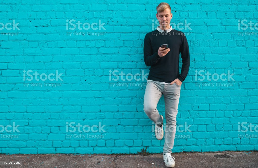 Young man standing against wall and checking phone. stock photo