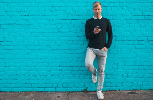 Young man standing against wall and checking phone. Young man standing against wall and checking phone. generation z stock pictures, royalty-free photos & images