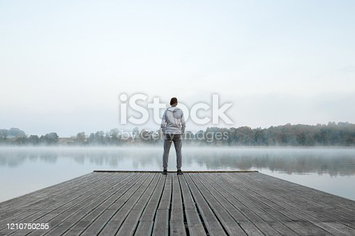 istock Young man standing alone on wooden footbridge and staring at lake. Thinking about life. Mist over water. Foggy air. Early chilly morning. Peaceful atmosphere in nature. Enjoying fresh air. Back view. 1210750255