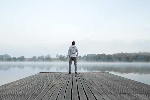 Young man standing alone on wooden footbridge and staring at lake. Thinking about life. Mist over water. Foggy air. Early chilly morning. Peaceful atmosphere in nature. Enjoying fresh air. Back view.
