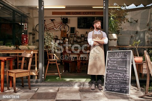 istock Young man standing at the entrance of his coffee shop 509373416