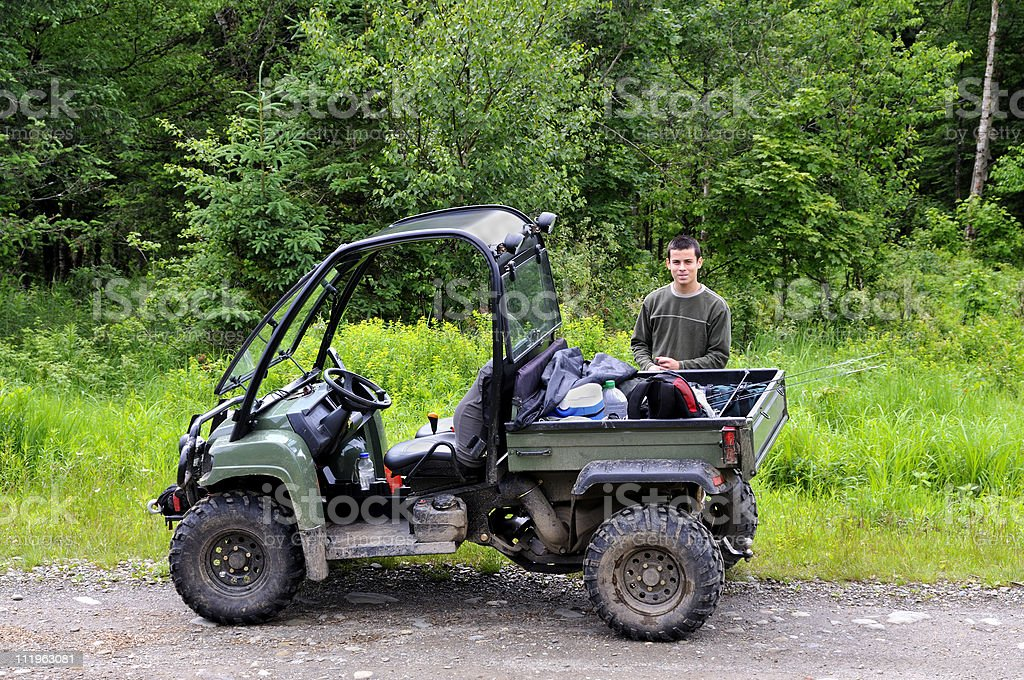 Young man standing behind four wheeler royalty-free stock photo