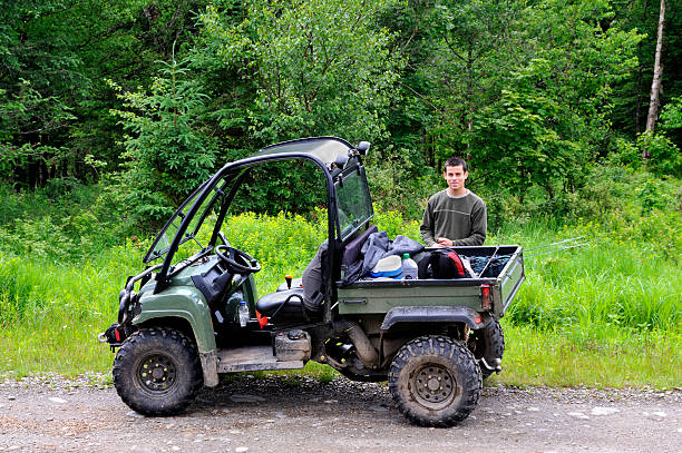 Young man standing behind four wheeler stock photo