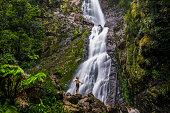 Young man standing below waterfall, with green moss and dense rainforest environment, Tasmania, Australia