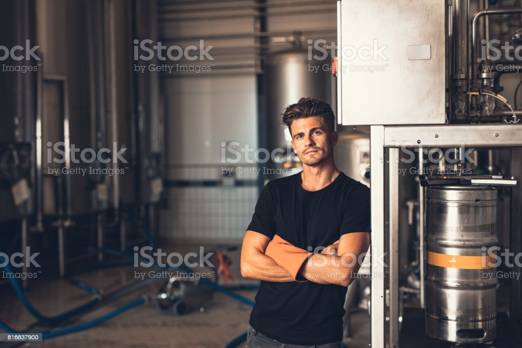Young man standing by beer filling machine stock photo