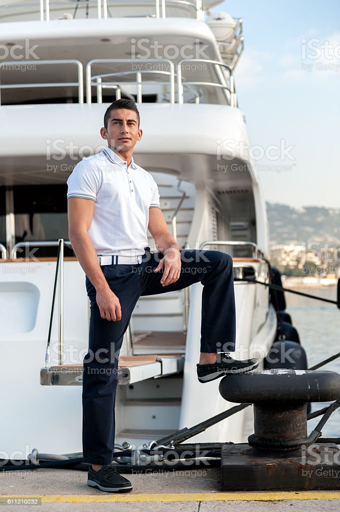 Young man standing by ferry at dock stock photo