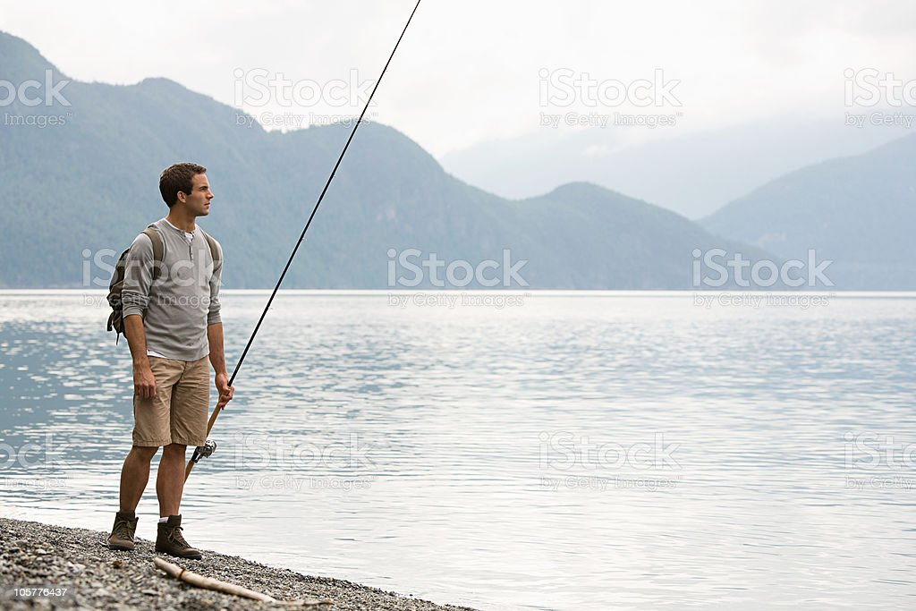 Young man standing by lake with fishing rod royalty-free stock photo