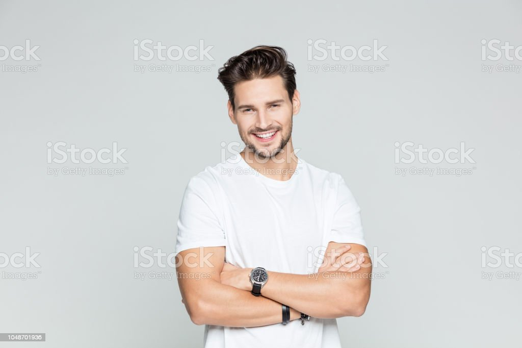 Young man  standing confidently Portrait of young man standing with his arms crossed smiling on grey background 25-29 Years Stock Photo