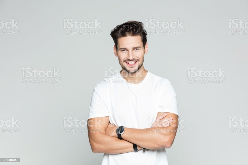 Young man standing confidently Portrait of attractive young caucasian man over grey background. Male model standing with his arms crossed and smiling. 25-29 Years Stock Photo