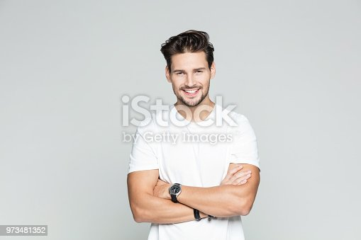 Portrait of attractive young caucasian man over grey background. Male model standing with his arms crossed and smiling.
