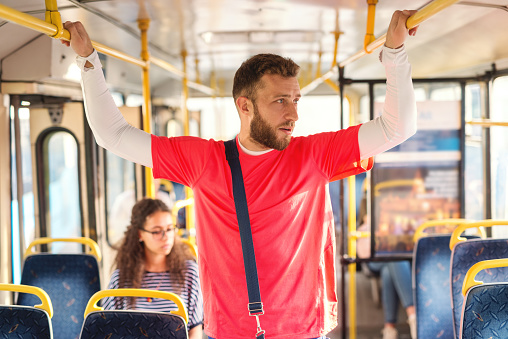 Young man standing in a bus, holding to hand-grip , looking trough window, thinking.