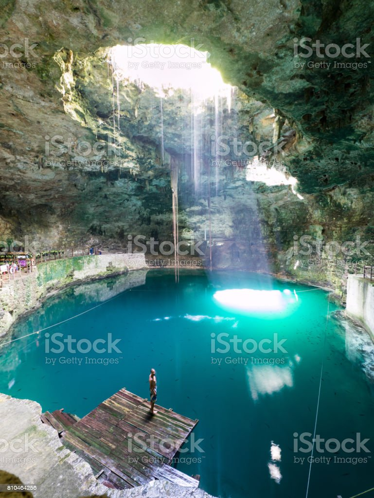 Young man standing in cenote Hubiku in mexico stock photo