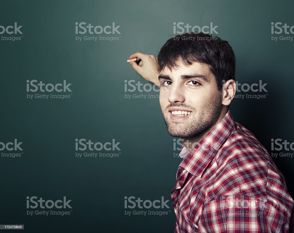 Young man standing in front of a blackboard royalty-free stock photo