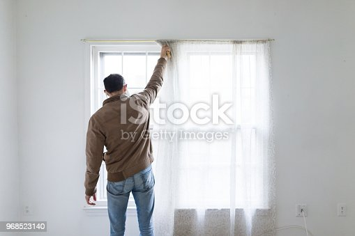 Young man standing in front of bright window in room adjusting blinds curtains, white painted walls, during remodeling, cleaning, inspection